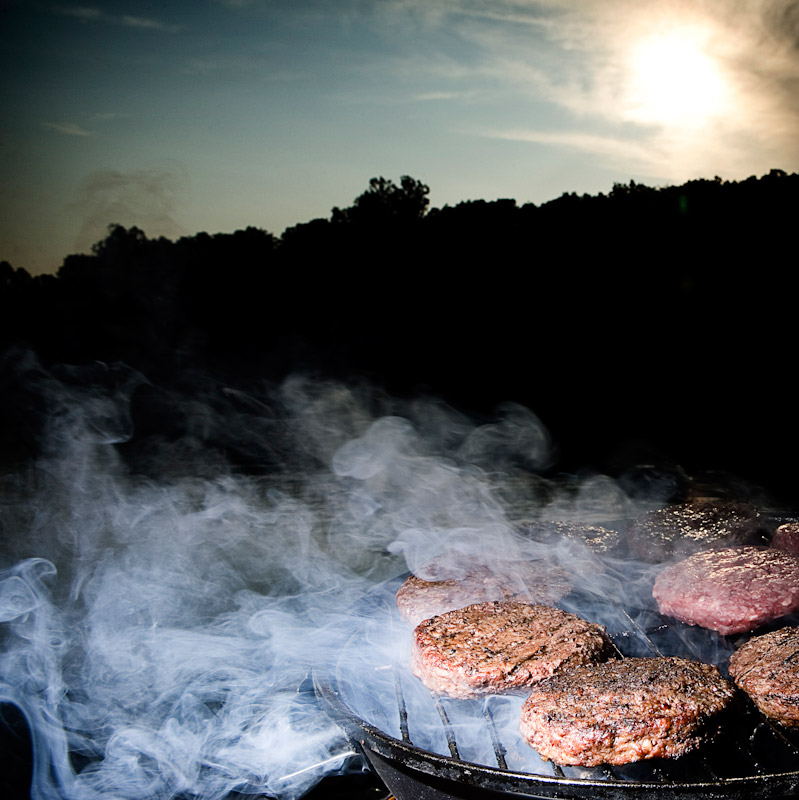 Burgers cooking on a grill during sunset.