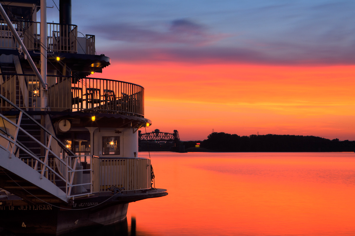 A steamboat is docked on the Ohio River as the sun sets