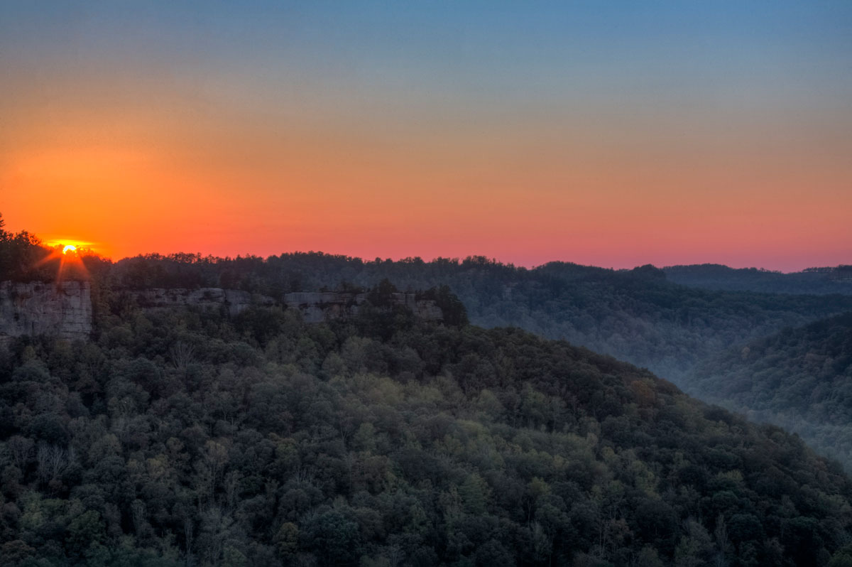 The sun sets as fog starts to roll through the valley.