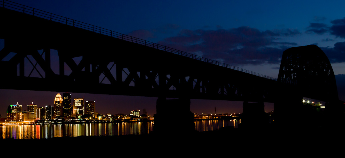 Downtown Louisville reflects in the water of the Ohio River beneath a train bridge.