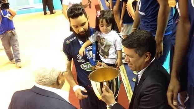 William com a filha e o troféu de campeão no colo