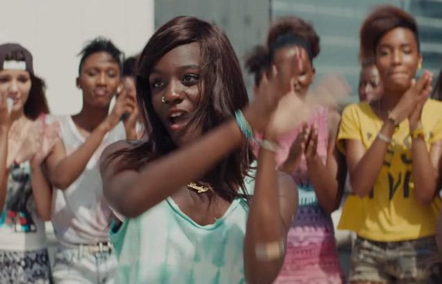 a black teenage girl dances as people look on