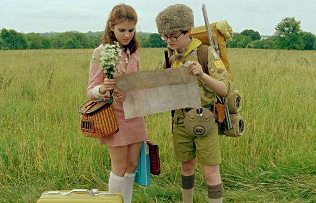 a boy and girl in sixties clothing look at a map in a field