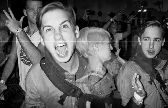 a black and white shot of lots of young people at a crowded punk club