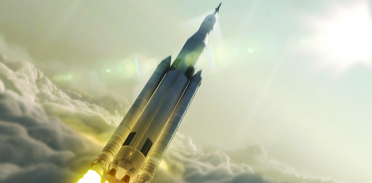 An image is shown of a rocket that appears to have just passed through a layer of clouds as it travels skyward. A bright white light is seen in the upper right corner of the image. To the lower left appears the layer of clouds and the bottom of the rocket with fire projecting from the fuel cones at its base.