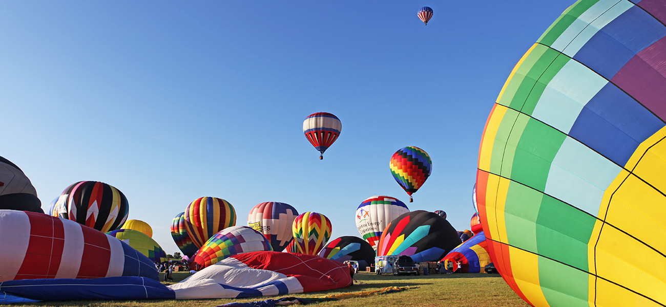 A photograph shows about twenty colorful hot air balloons at varying stages of inflation. Some are deflated, while others are inflated. Three of the balloons are off the ground and are visible against a bright blue sky.