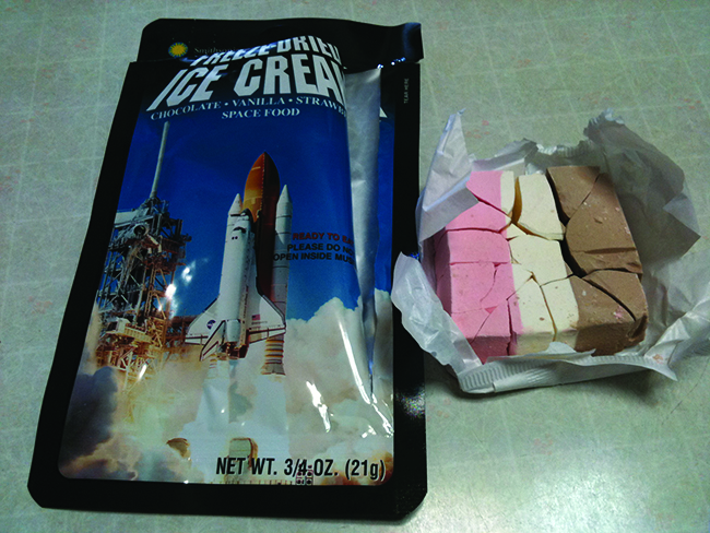 A photograph shows a package with a rocket being launched on the front and a block of pink, white and brown striped solid in a wrapper next to it.