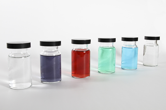 This figure shows six containers. Each is filled with a different color liquid. The first appears to be clear; the second appears to be purple; the third appears to be red; the fourth appears to be teal; the fifth appears to be blue; and the sixth also appears to be clear.