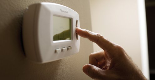 Image features a close-up image of a person adjusting a thermostat.