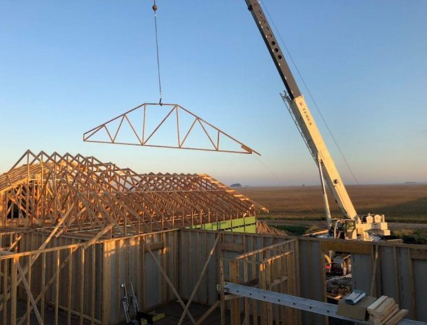 Photo of crane lifting roof truss to a house top