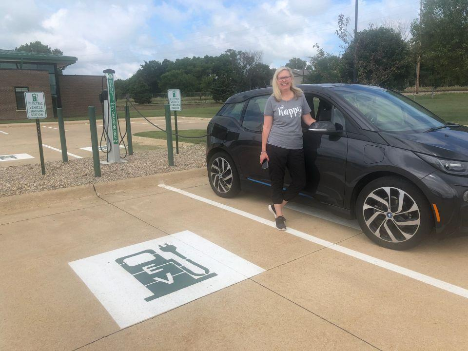 Customer standing by car while she uses Iowa Lakes charging station to charge her electric vehicle