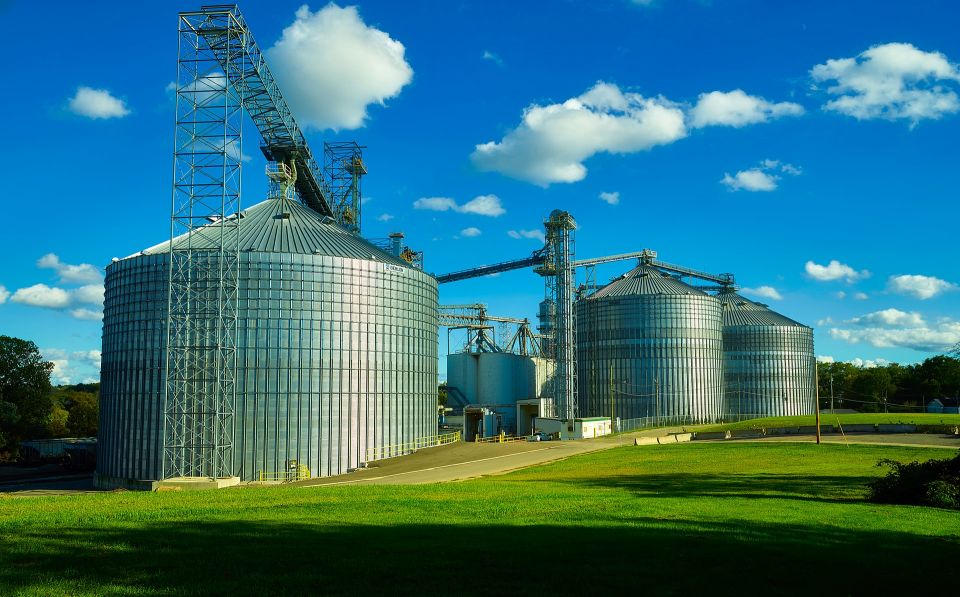 Grain bins, blue sky with clouds, green grass