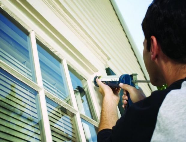 male homeowner caulking a window