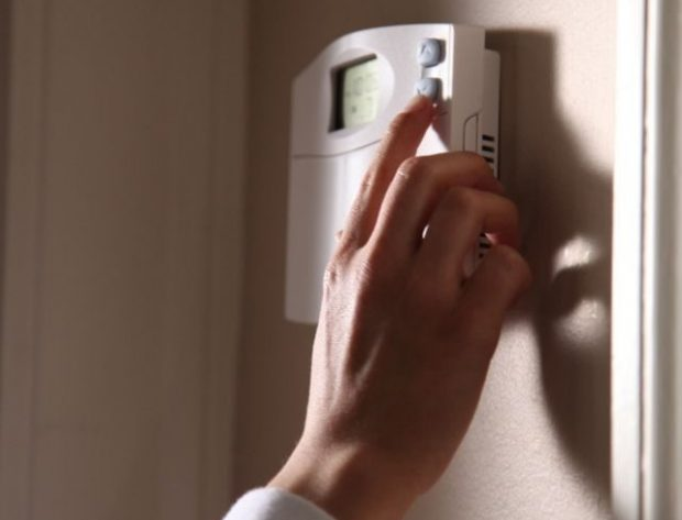 Woman adjusting temperature on wall thermastat