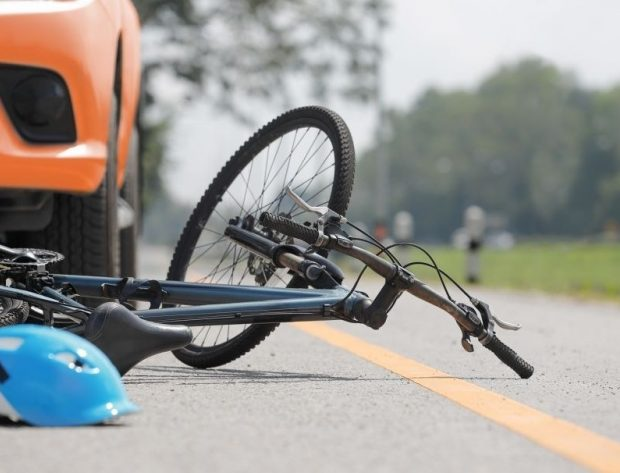 Tipped bike and helmet in front of vehicle