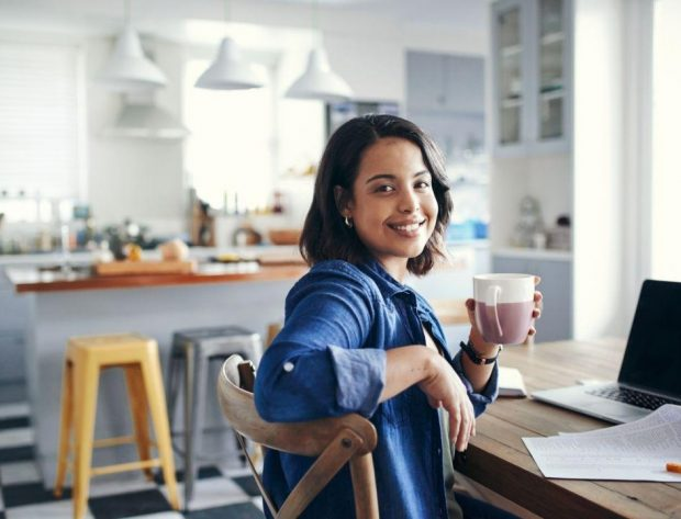 Photo of young woman working at home and sitting by her desk and computer. She is holding a coffee cup.