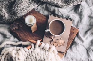 A cozy scene with blankets, a candle, notepad and a cup of hot chocolate.