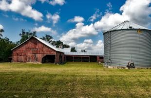 Grain bin on farm, partly cloudy skies