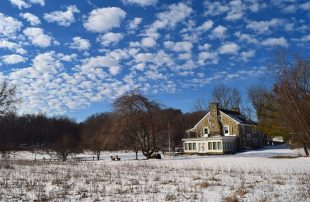 House surrounded by trees on snow covered ground with clouds in sky