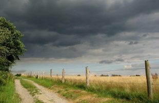 gravel road, fence, dark clouds in the sky