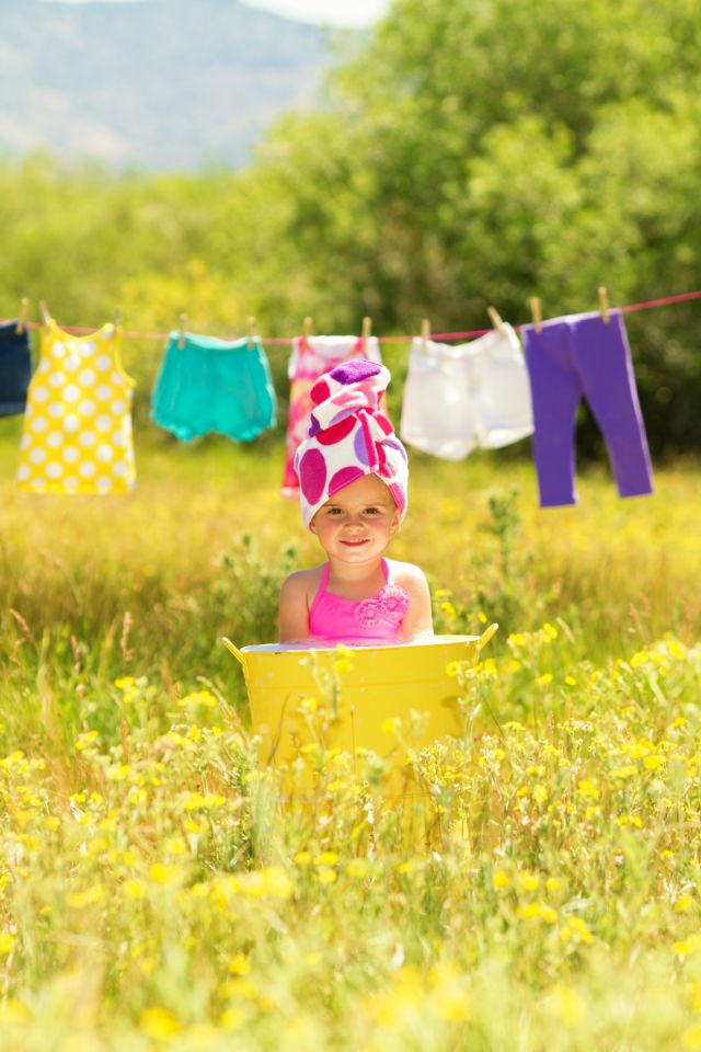 Clothes hanging on line with a child in a yellow tub in the grass
