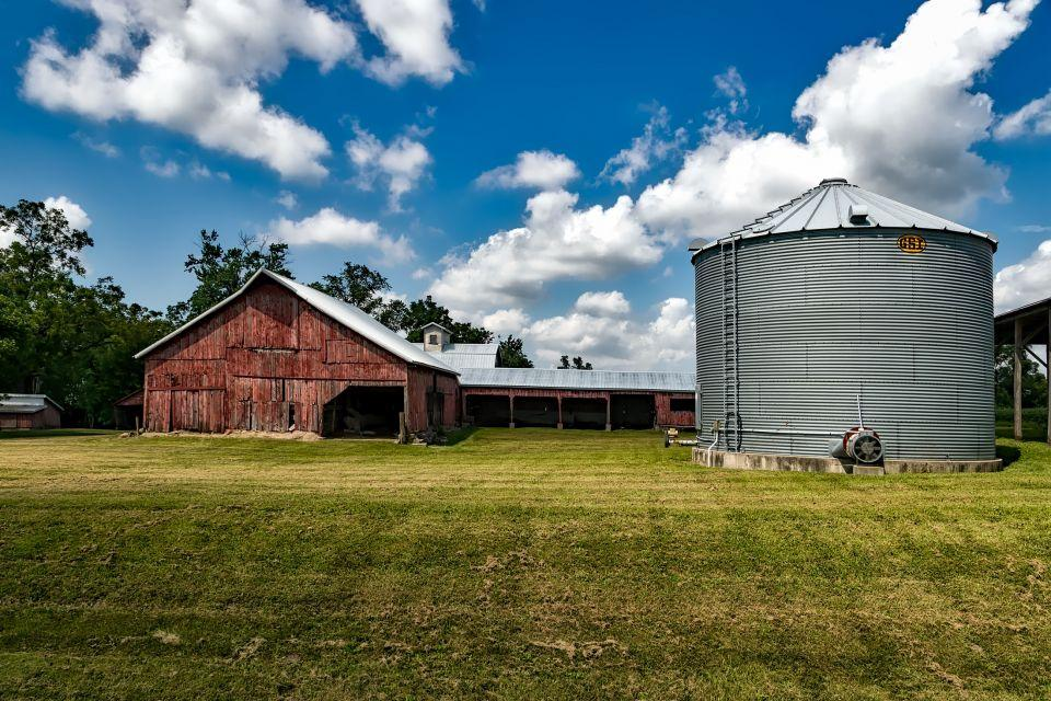 Grain bin with red rustic barn. Blue sky with some clouds.