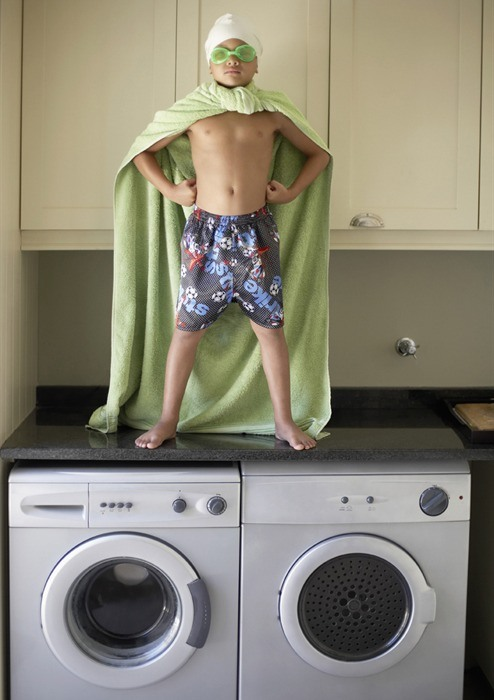 boy in cape on top of washer and dryer