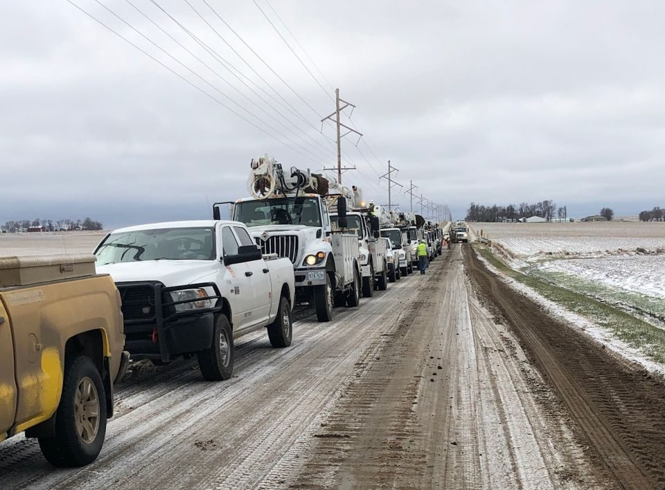 Several work trucks line up on the side of the road as line worker crews repair the damaged electric infrastructure
