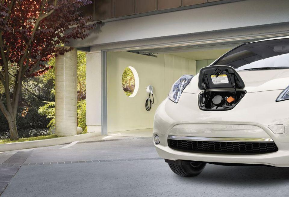 Image of an electric vehicle parked in a residential garage and its charger