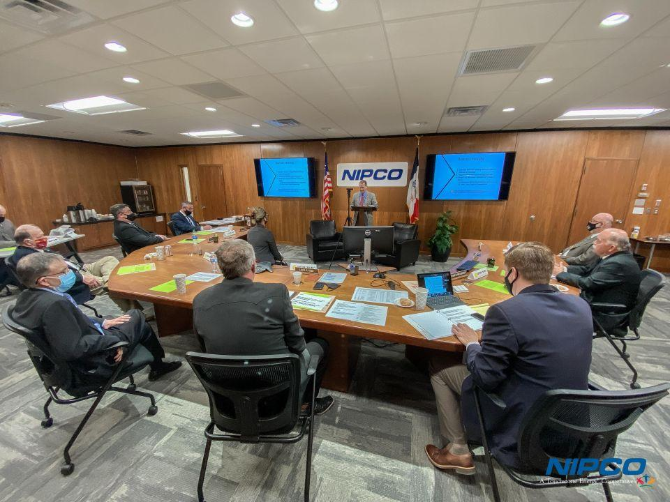Photo of NIPCO staff and directors sitting at the board table, participating in the meeting.