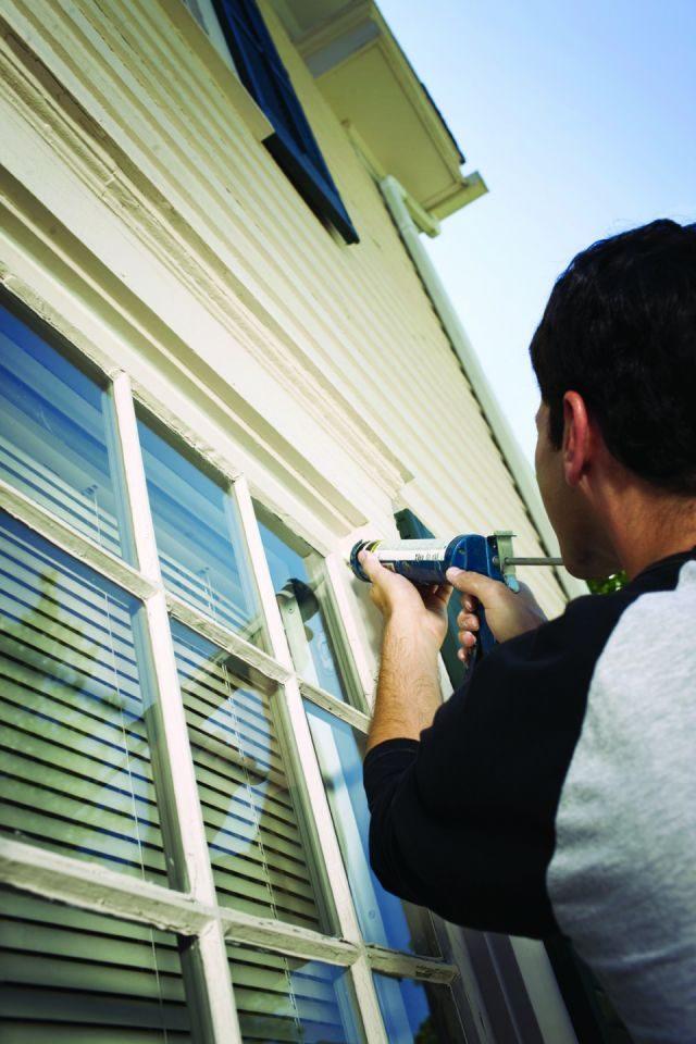 male homeowner caulking around a window
