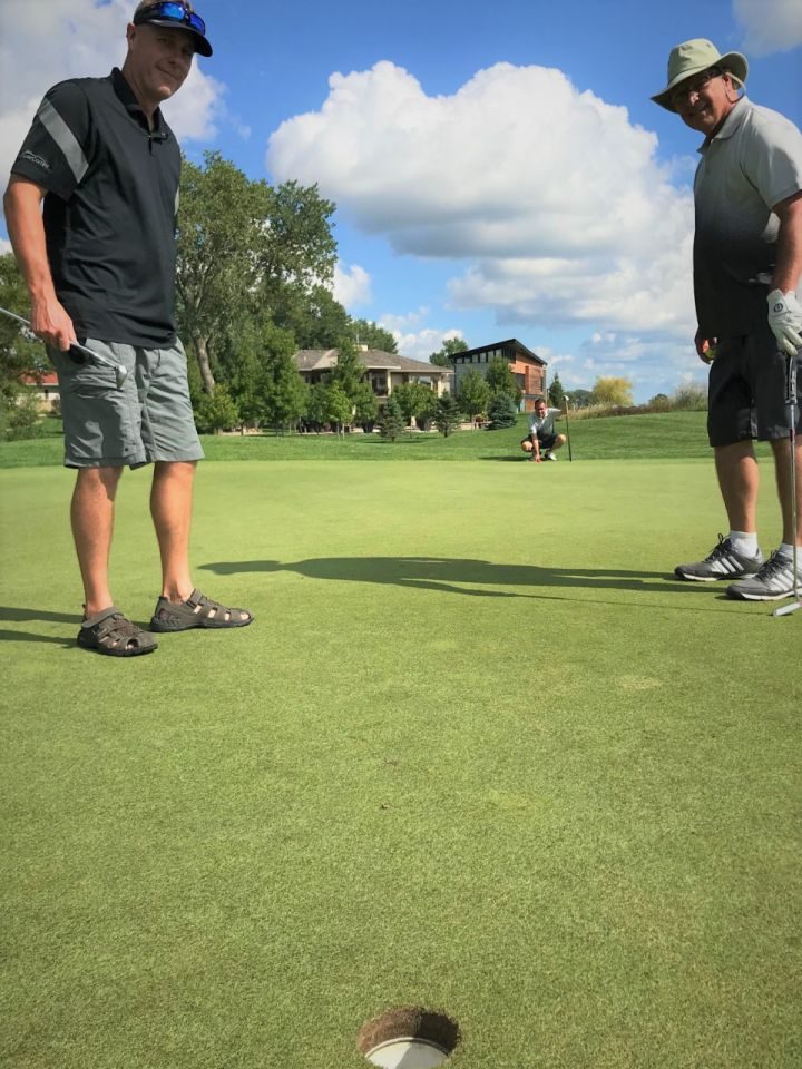 Golfers assess a fellow players' putting strategy.