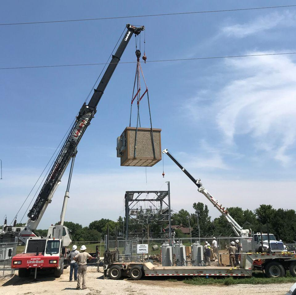 NIPCO crews lower a communication  building into a substation yard in Harla, Iowa.
