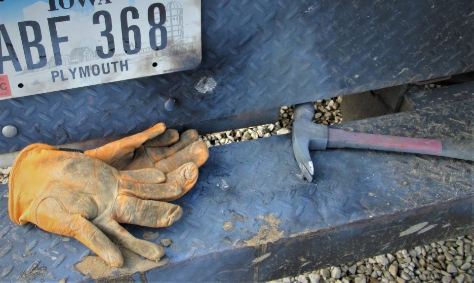 Image shows the back bumper of the truck where the injured crew member's gloves lay along withthe hammer that was fused with the truck bumper.