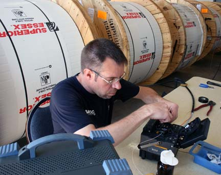 A NIPCO employee is pictured here splicing fiber optic cable.