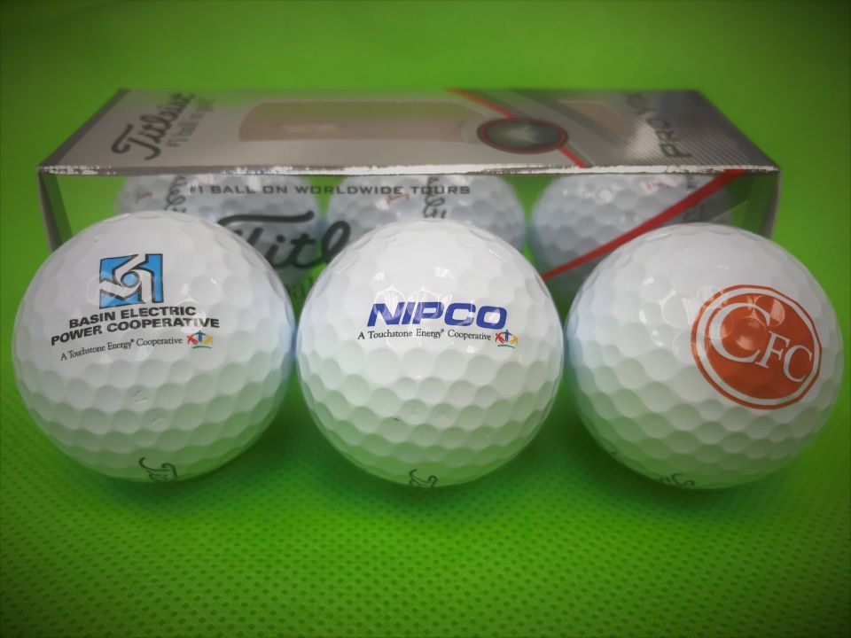 close-up photo of three golf balls and the box they come in