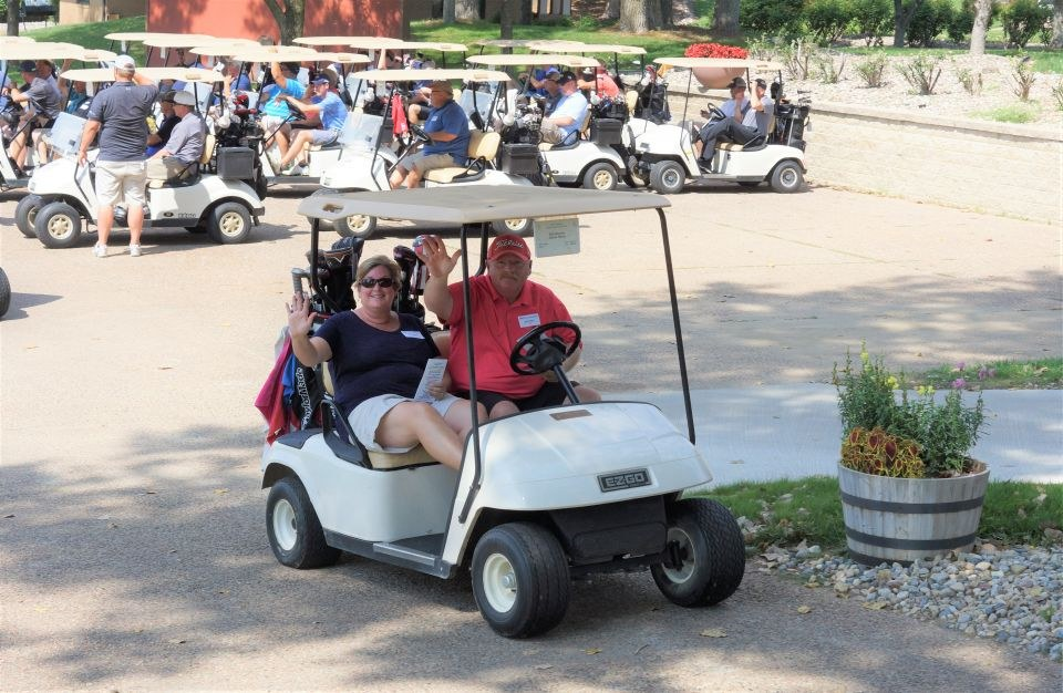 Two golfers wave, while riding in a golf cart