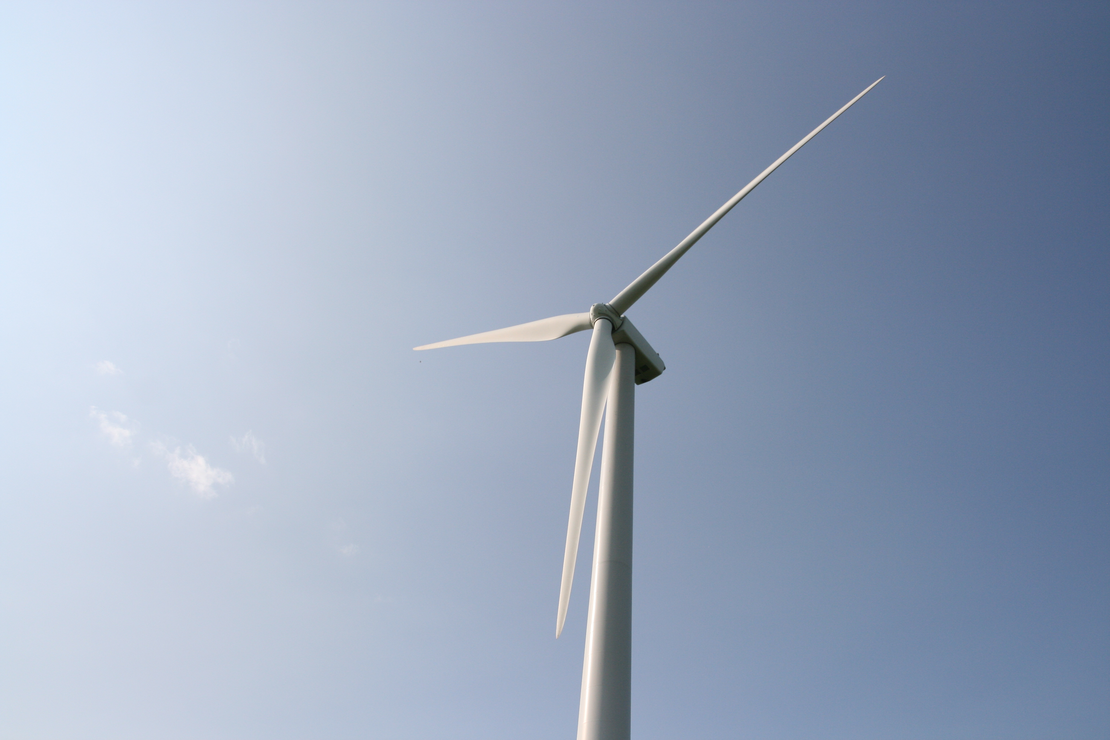image of a wind turbine against a blue sky background