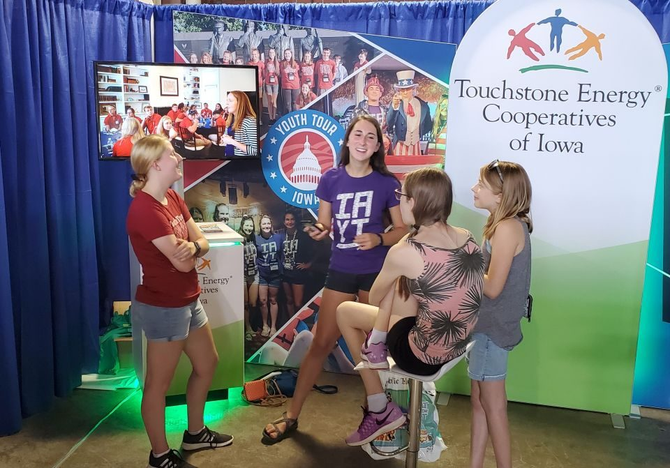 young fairgoers learning about cooperative leadership programs from youth tour alumni while standing in the booth