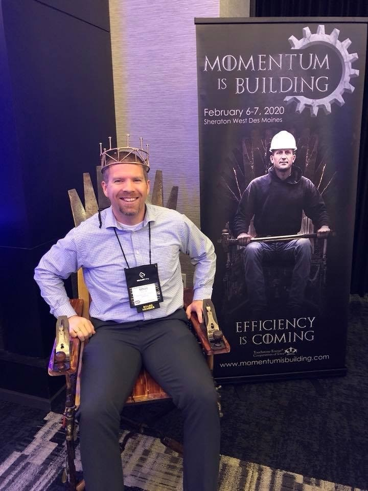 Photo of the Momentum is Building event banner and the specially-designed and adapted throne with a man sitting in it, wearing a crown.