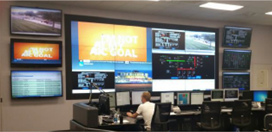 Photo image of a control operator, seated at a desk, with multiple 55-inch monitors in front of him, displayed on a wall.
