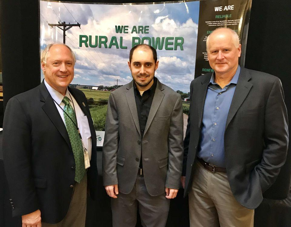 """Two men from North West REC stand with Iowa Representative Tom Jeneary in front of a background image that reads: """"We are rural power"""""""