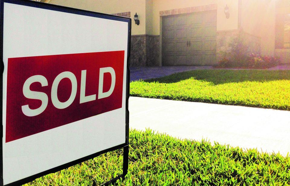 "Real estate sign in the lawn of a home with the word ""SOLD"" on it"