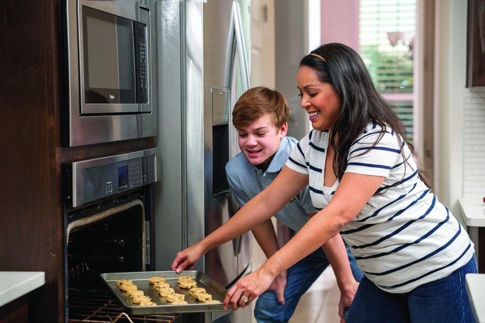 Photo image of mother and son putting cookies into an oven.