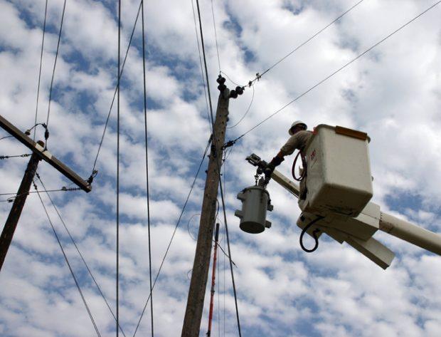 Lineman in a bucket near poles