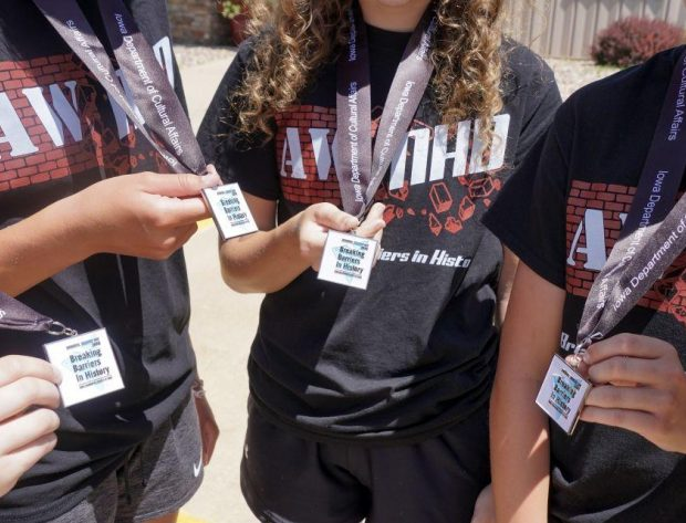 Extreme close-up photo of students holding their medals.