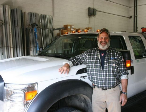 Photo image of Bruce Christensen standing by a NIPCO work truck.