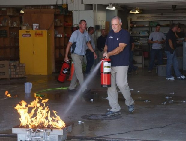 Photo of NIPCO employee performing fire extinguisher training.