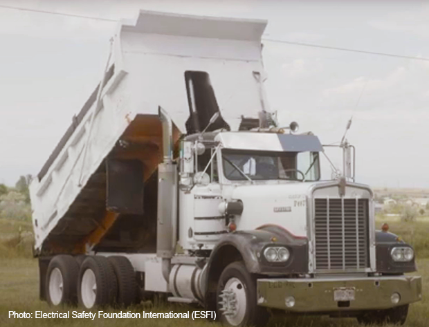 Photo image of a dump truck with its dumper raised dangerously close to a power line.