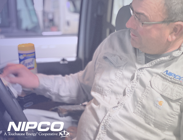Photo of a NIPCO crew member disinfecting the steering wheel of his utility truck, using a Lysol wipe.